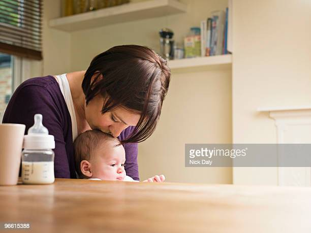 Mother kissing her baby in the kitchen