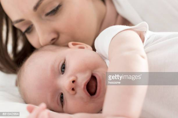 Mother kissing her daughter on bed