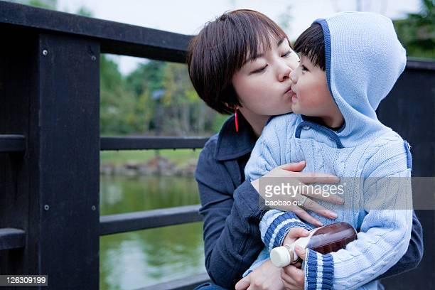 Mother kissing her kid on bridge in park