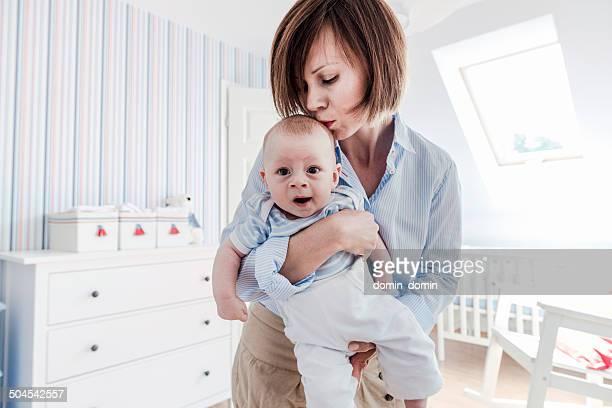Mother kissing her sleepy little baby boy gently, baby's room