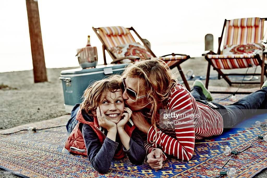 A mother kissing her son on a blanket. : Stock Photo