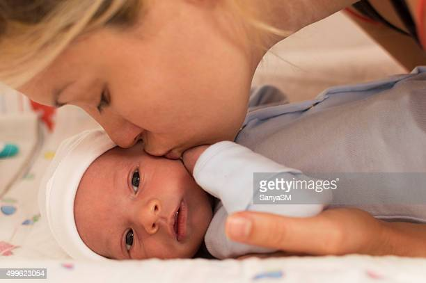 Mother kissing newborn baby boy