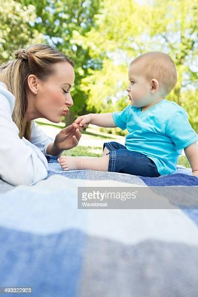 Mãe Beijar a Mão de Bebê Menino no parque