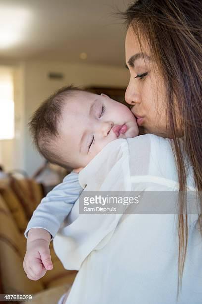 Mother kissing sleeping baby girl