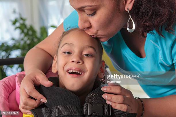 Mother kissing small daughter with Cerebral Palsy