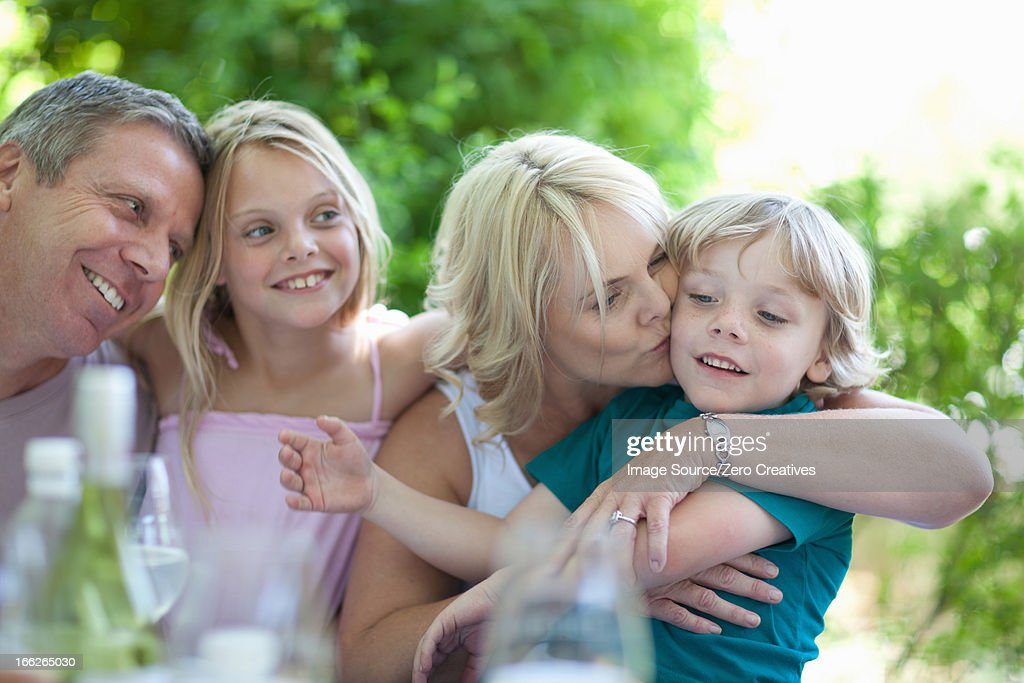 Mother kissing son at table outdoors : Stock Photo