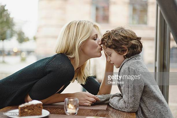 Mother kissing son in a café