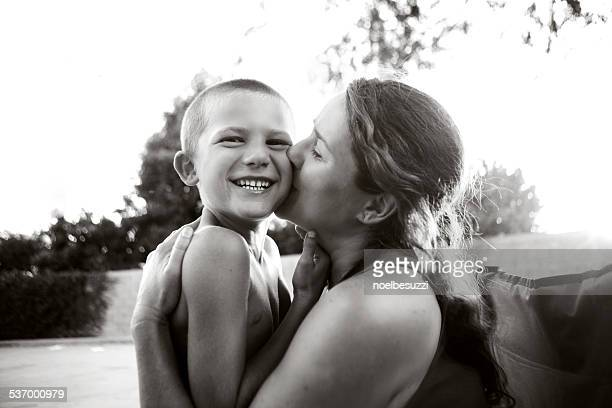Mother kissing son in park