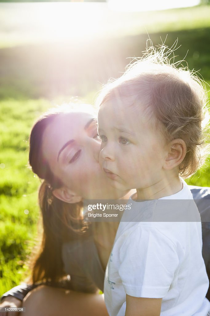 Mother kissing toddler in park : Stock Photo