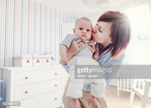 Mother kissing unhappy little baby boy, home interior, retro look