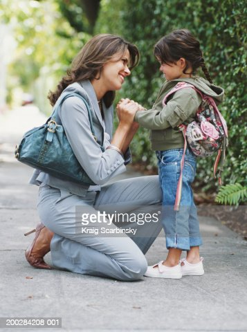 Mother kneeling on pavement, holding hands of daughter (4-6 years), smiling, side view