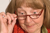 Close up of a senior adult female wearing glasses pursing her lips in disapproval at the camera.  This senior citizen wants to tell the viewer exactly what she thinks, because her opinion should be ju