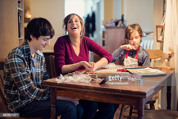 Mother laughing with sons making gingerbread cookie at home.
