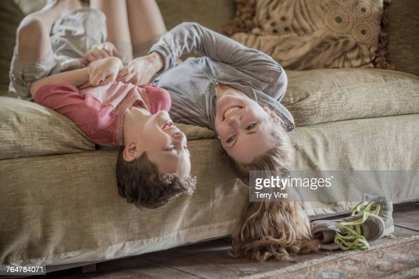 Mother laying upside-down with son on sofa