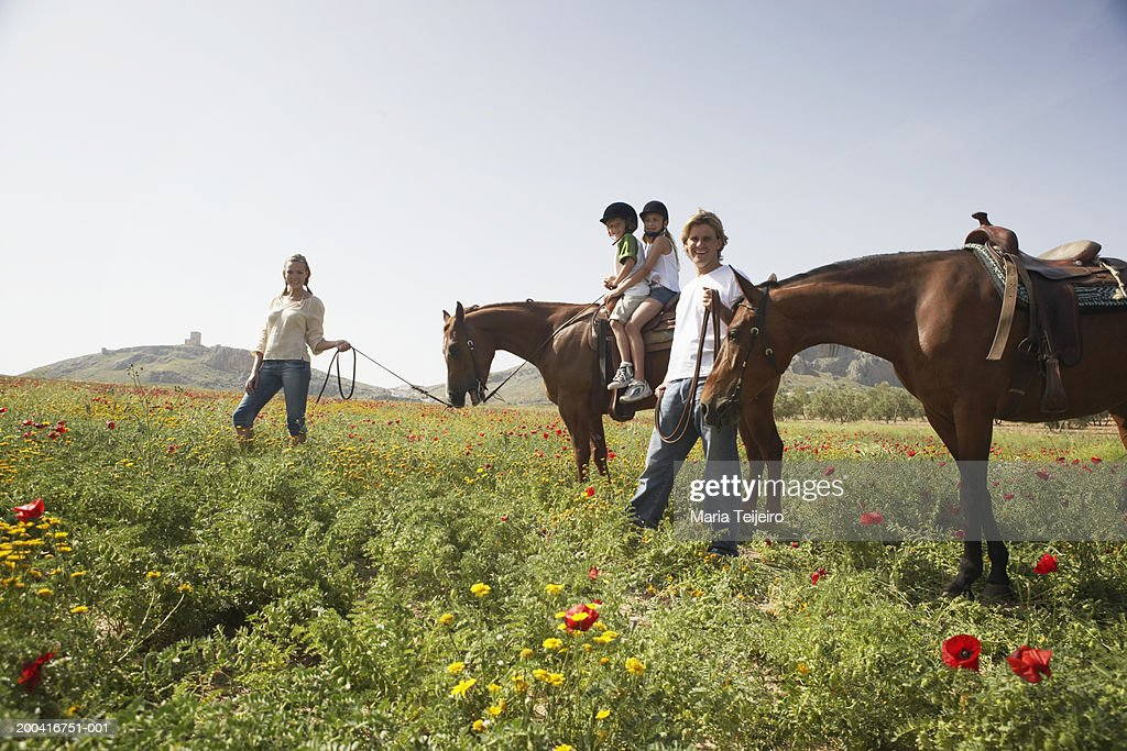Mother leading son and daughter (9-11) on horse by father and horse