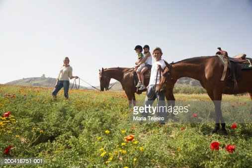 Mother leading son and daughter (9-11) on horse by father and horse : Stock Photo