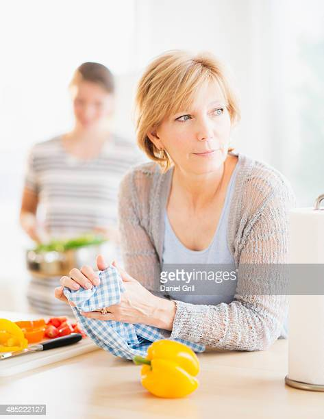 Mother leaning on kitchen counter, out-of-focus daughter in background