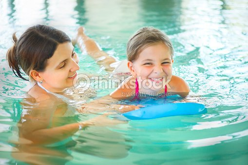 21517f55b5 Mother learning to swim her little daughter indoor swimming pool : Stock  Photo