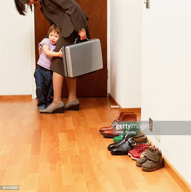 Mother leaving for work with child clinging on.