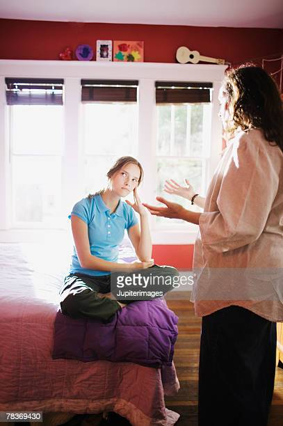 Mother lecturing sulking preteen girl