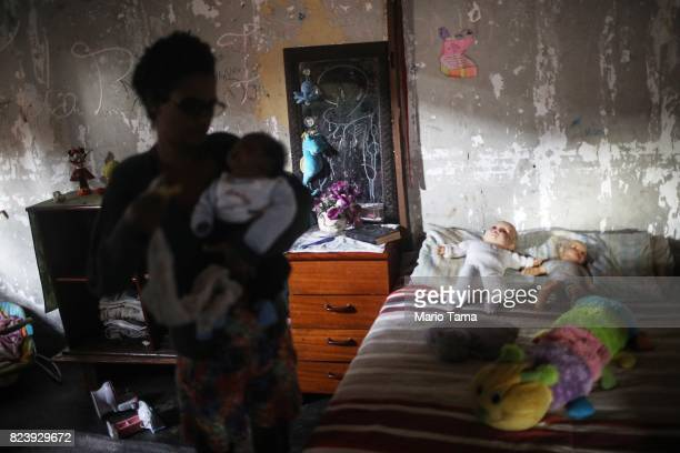 Mother Lianna holds her newborn Lucas in their house in a set of occupied buildings in the Mangueira 'favela' community on July 24 2017 in Rio de...