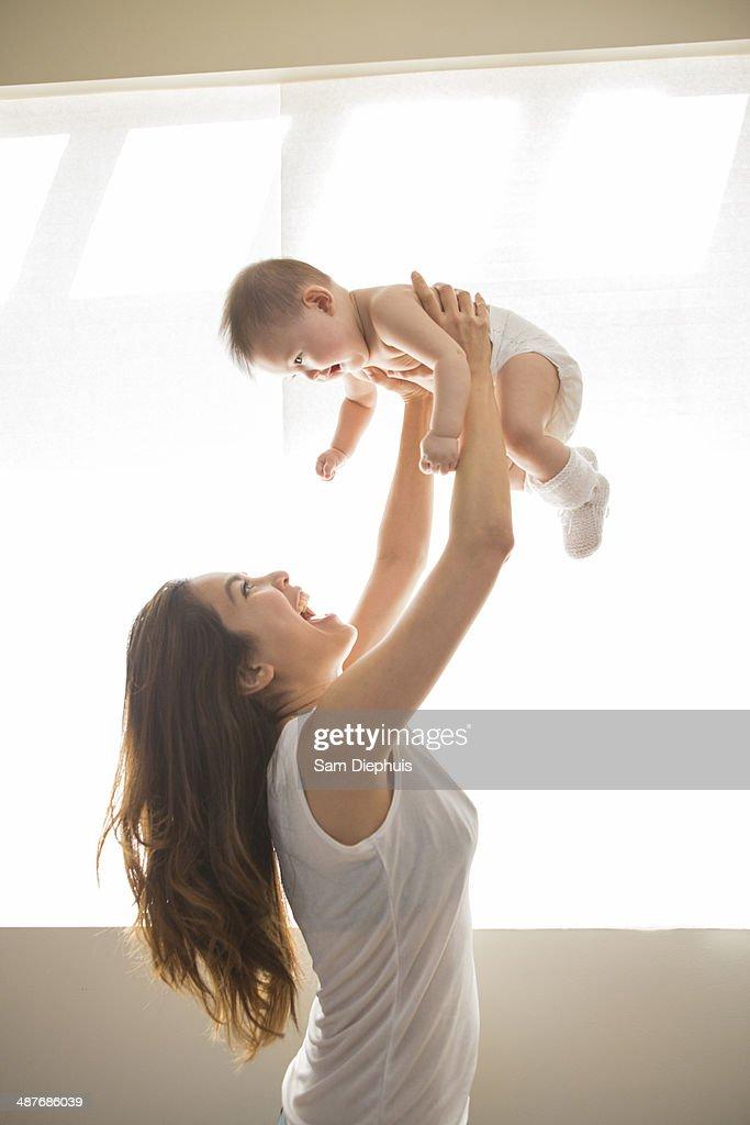 Mother lifting baby girl overhead
