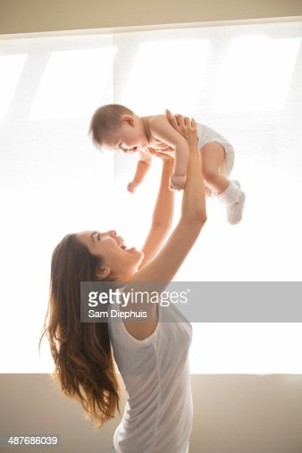 Mother lifting baby girl overhead