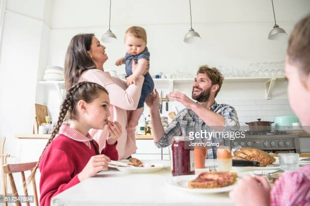 Mother lifting baby son and passing over to father, girls eating breakfast