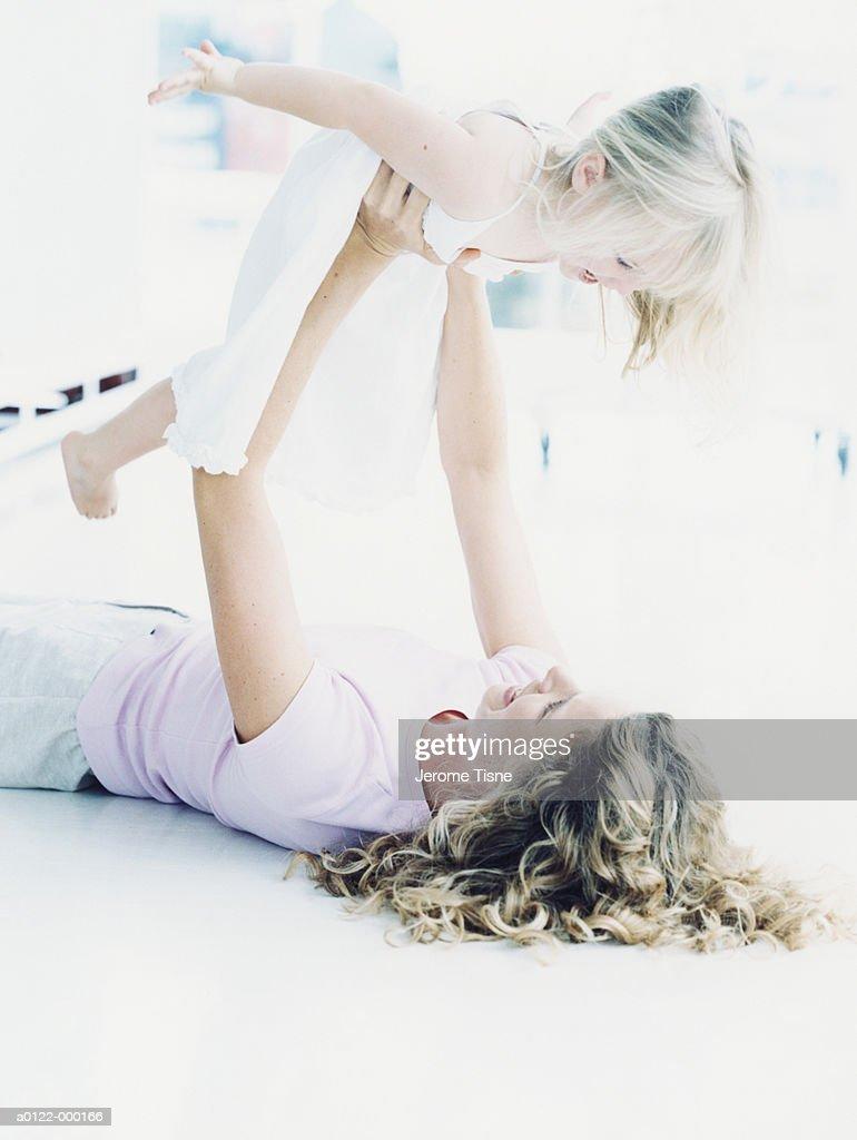 Mother Lifting Daughter : Stock Photo