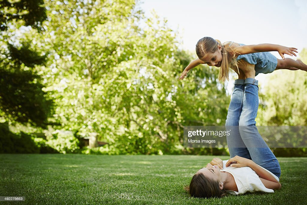 Mother lifting daughter with legs in park : Stock Photo