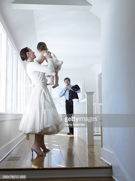 Mother lifting female toddler (18-21 months), looking towards father