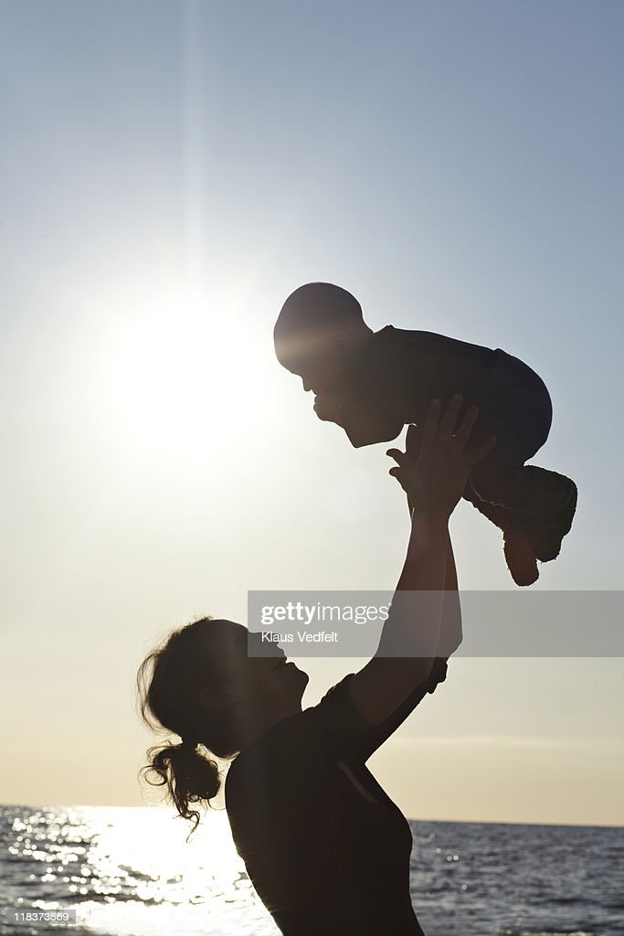 Mother lifting up baby boy on the beach : Stock Photo