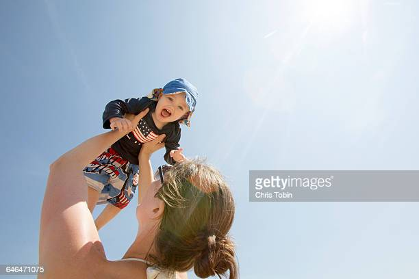 Mother lifting up child into the air