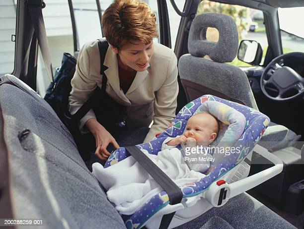 Mother looking after child laying in seat
