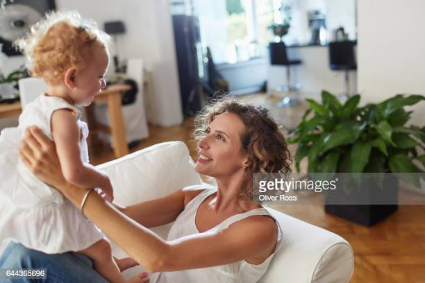 Mother looking at baby girl at home