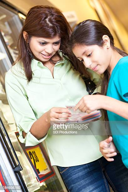 Mother looking at coupons with daughter in the grocery store