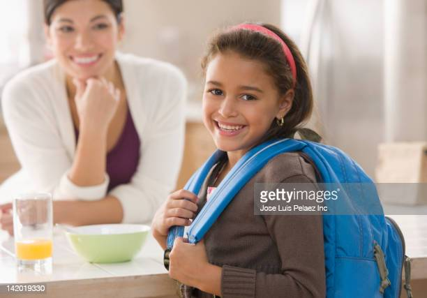 Mother looking at daughter wearing backpack