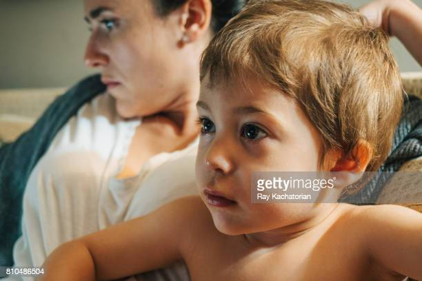 Mother looking at mobile device and child watches TV