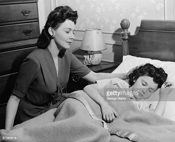 Mother looking at sleeping daughter (8-9), (B&W)
