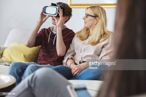 Mother looking at son using virtual reality headset while sitting on sofa