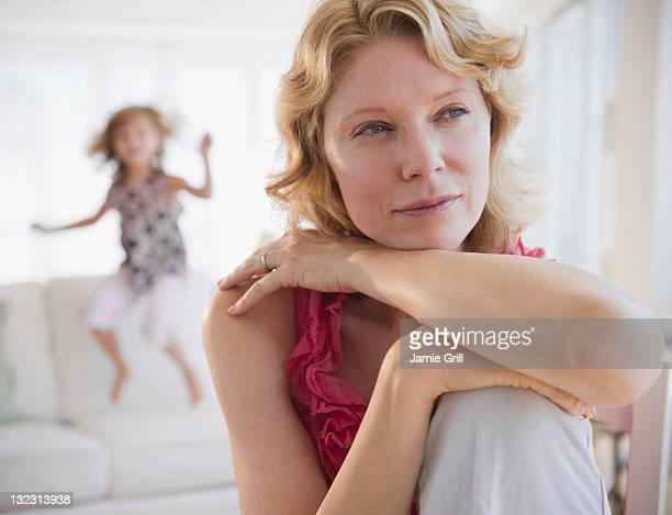 Mother looking away while daughter jumps on couch