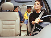 Mother looking into rear-view mirror watching children