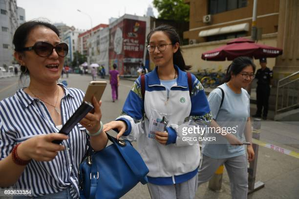 A mother looks at photos she took of her daughter after she finished a college entrance exam at a school in Beijing on June 8 2017 Millions of...