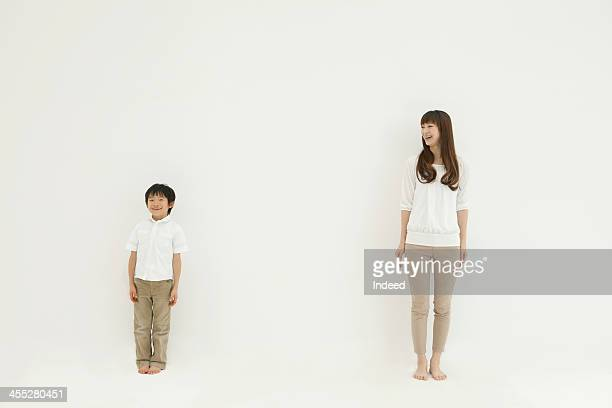 mother looks at son in front of the white background