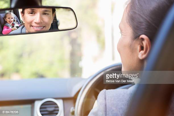 mother looks in backmirror at daughter in car.