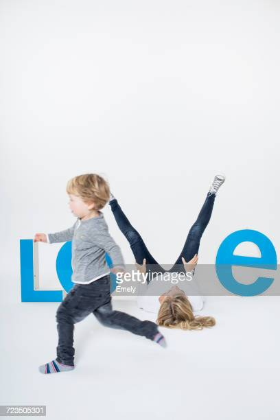 Mother lying on floor between three-dimensional letters, creating the word LOVE, young boy running across frame