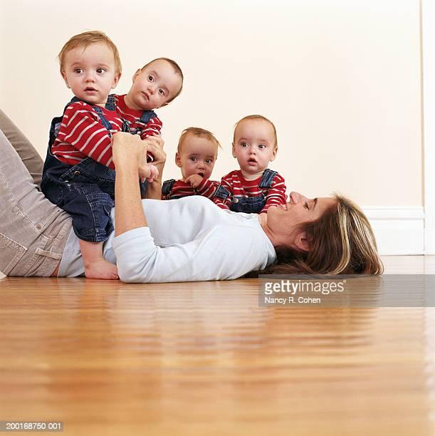 Mother lying on hardwood floor with quadruplet babies (9-12 months)