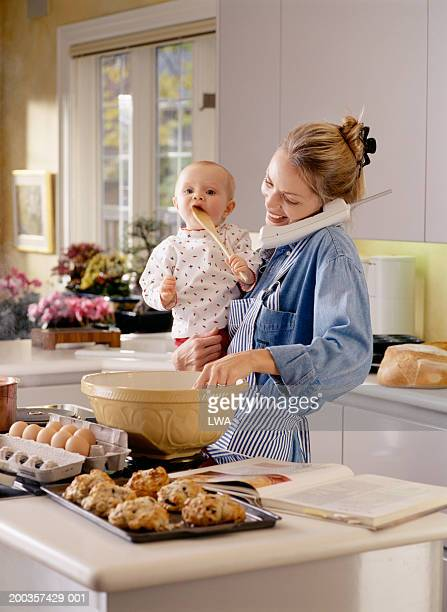Mother making batter, holding baby girl (9-12 months), using telephone