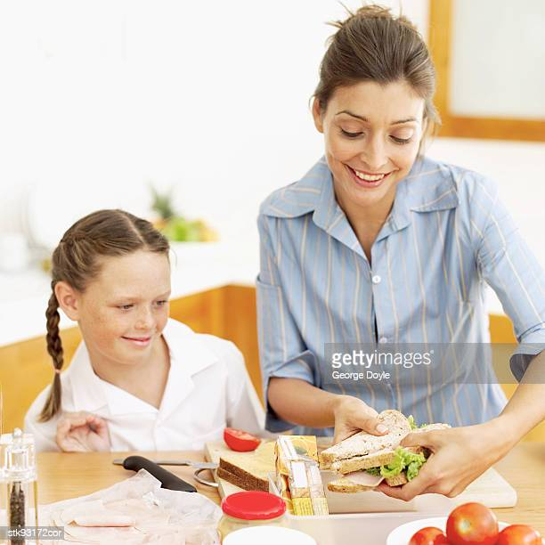 mother making her daughter's (6-7) school lunch