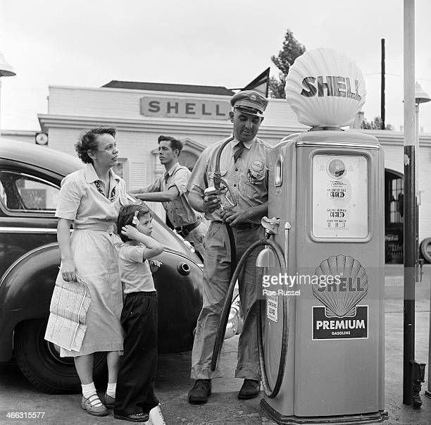 A mother map in hand and her young daughter ask a question of a Shell gas station attendant as he fills up the tank of their car Virginia 1949